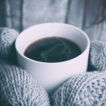 Heating Costs person holding cup of hot coffee with gloves on